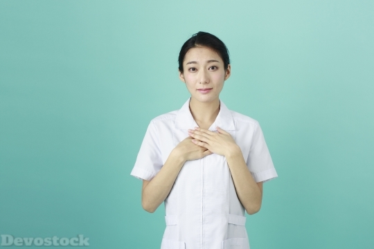 Devostock FEMALE NURSE HITTING HER HAND ON HER CHEST