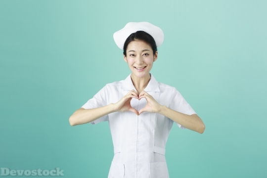 Devostock FEMALE NURSE MAKING HEART BY HAND