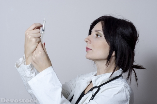 Devostock Girl FEMALE DOCTOR WATCHING SYRINGE