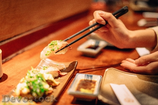 Devostock GRASPING SUSHI GRABBED WITH CHOPSTICKS
