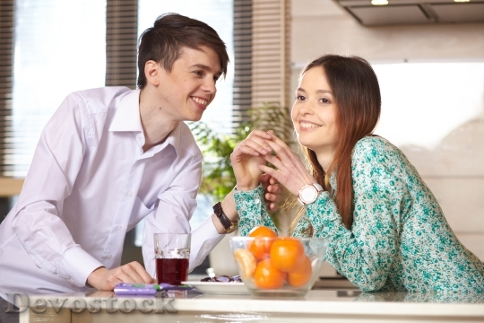 Devostock Young Couples Talking Kitchen 4K