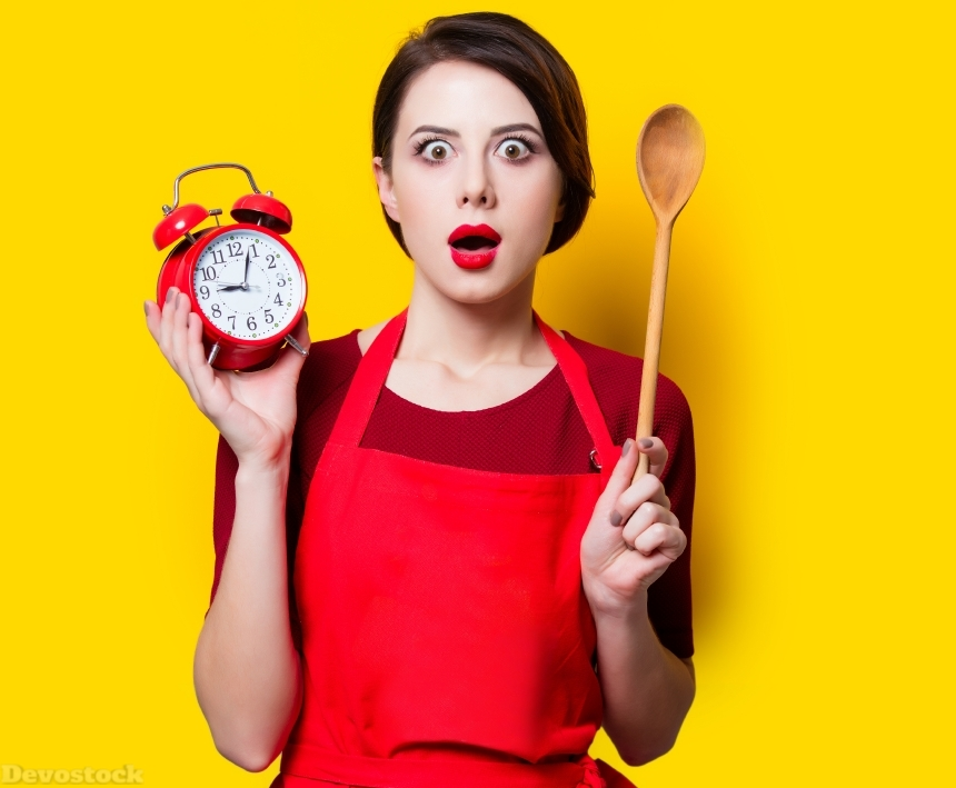 housewife with red alarm clock and spoon