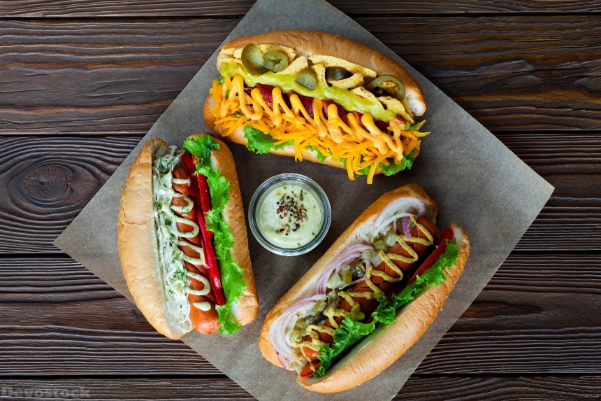Devostock Assorted three hot dogs with sauce and salad on a wooden backgro