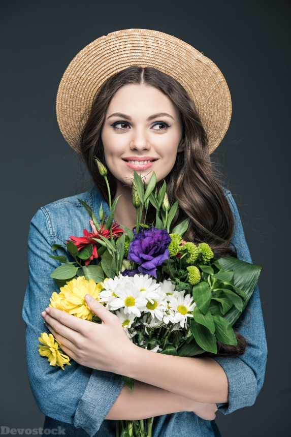 Devostock beautiful cheerful girl in straw hat holding flowers for interna