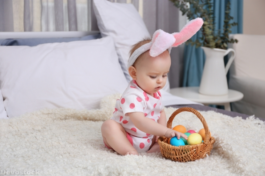 Devostock Cute funny baby with bunny ears and basket full of Easter eggs a