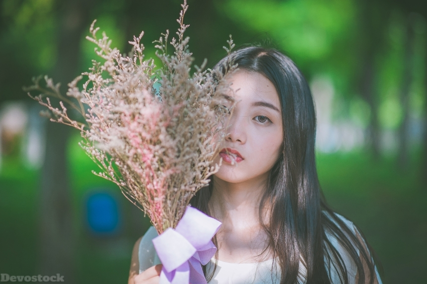 Devostock Asian Beautiful Girl Holding bunch Leaves Spring Love Passion Nature 4k