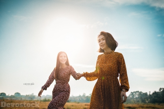 Devostock Beautiful Two Women GRASS HOLDING HANDS Sisterhood 4k