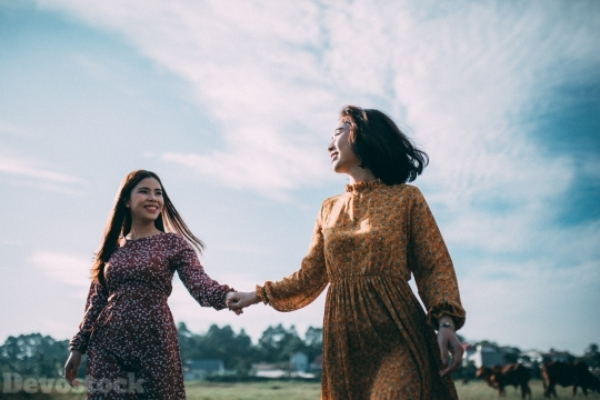 Devostock Beautiful Two Women GRASS HOLDING Smiling HANDS Sisterhood 4k