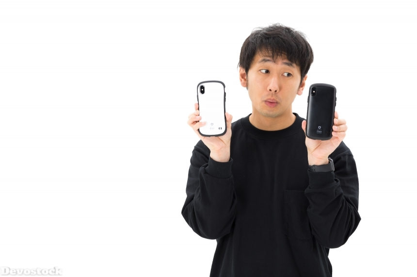 Devostock Man Two Mobiles White Background Comparing 4k