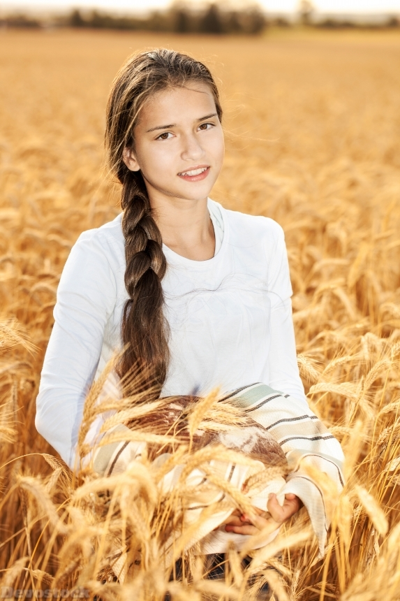 Devostock Happy girl on field of wheat with bread