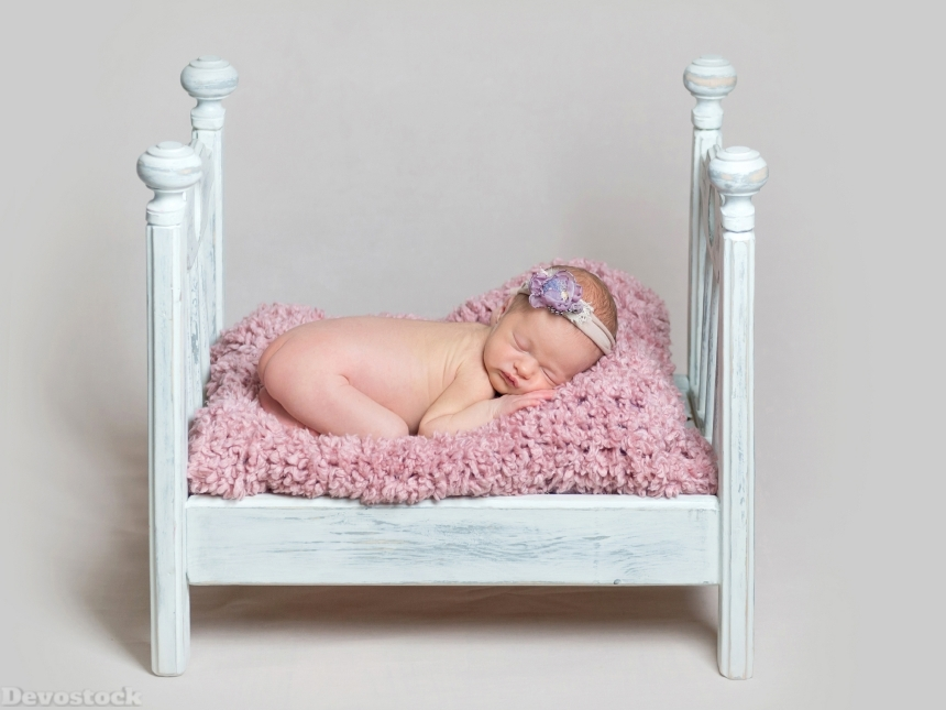 Devostock Lovely newborn baby girl sleeps on the crib