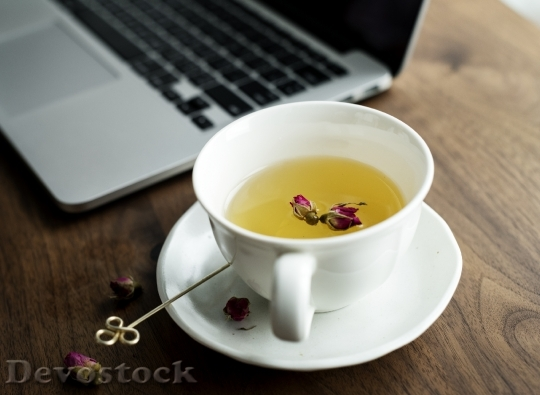 Devostock A cup of nice herbal tea next to a computer laptop
