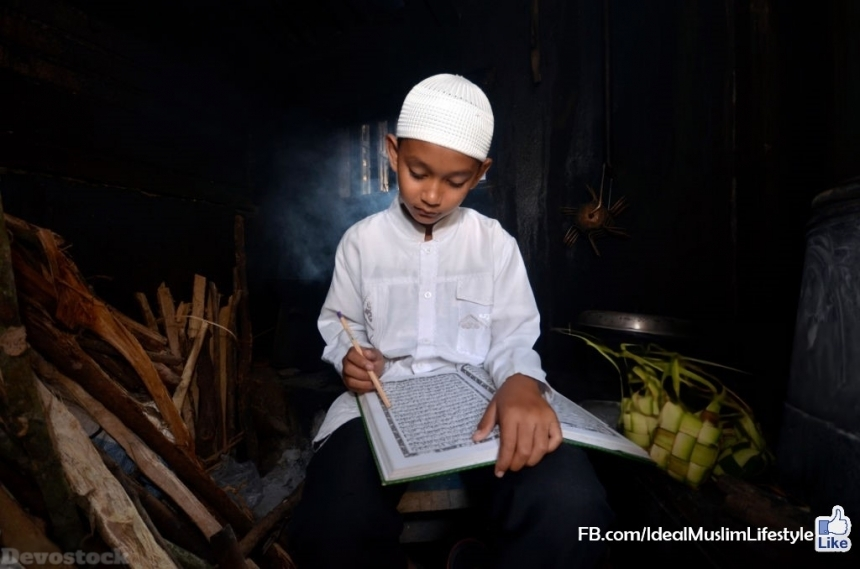 Devostock A Muslim boy reading Al Quran