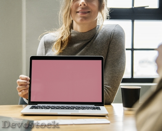 Devostock Blond woman pointing at a laptop screen