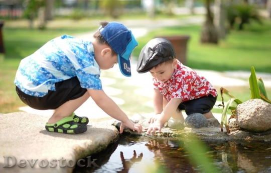 Devostock Little boys playing with water of the lake