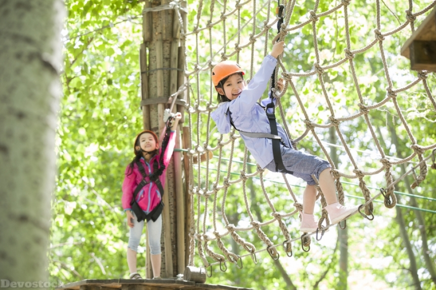 Devostock Little girls playing in tree top adventure park