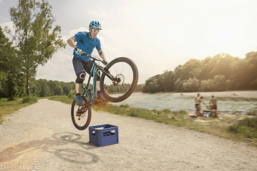 man jumping with mountainbike over beer box near river,sunset,acrobatic