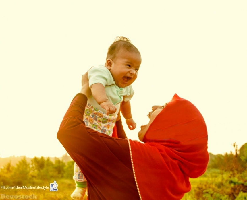 Muslim mother carrying her smiling baby