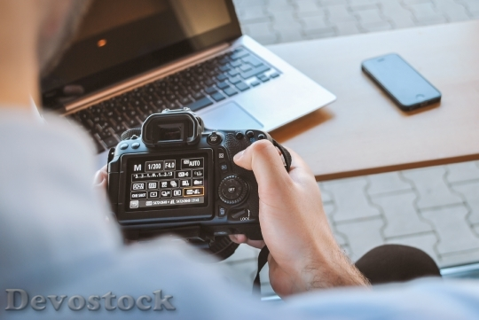 Devostock Photographer works with his DSLR Camera