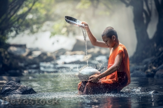 Devostock Selective focus photography of monk in river dripping water on stainless steel container